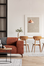 Open Plan Living And Dining Room Interior With Long Table With Chair And Brown Velvet Settee