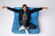One attractive smiling black man in a black jacket and black pants on a gray background sidin on a blue sofa