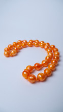Orange Beads On A White Background. Bright Accessories