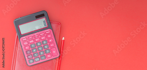Fotografía red calculator and organizer on the red table with red pencil
