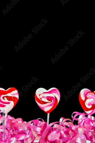 Fotografie, Obraz  Pink, Red and White Swirled Candy Lollipops With Pink Curling Ribbon with a Blac