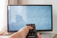 Hand With TV Remote Control In...