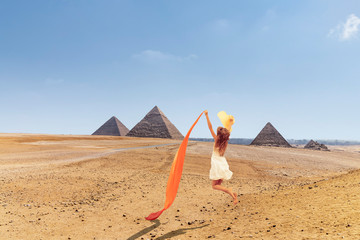 Happy woman jumping in the area with the great pyramids of Giza, Egypt