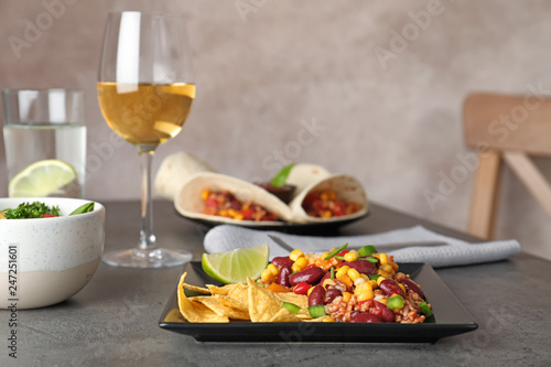 Plate with tasty chili con carne served on gray table