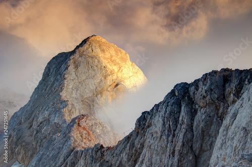 Fototapeta View from Triglav highest Slovenian summit to huge sharp ridge crest above sea of clouds with via ferrata route ascending from sunny Mali Triglav peak Julian Alps Triglav National Park Slovenia Europe obraz