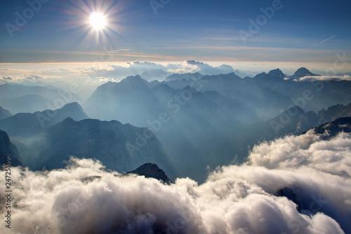 widok-ze-szczytu-triglav-z-niebieskimi-grzbietami-pasma-julijske-alpe-w-sloncu-bialymi-chmurami-o-niskim-haldzie-zamglona-dolina-trenta-soca-isonzo-i-szczytem-bavski-grintavec-park-narodowy-triglav-slowenia-europa