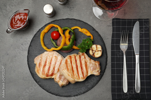 Grilled meat served with garnish, sauce and wine on grey background, top view