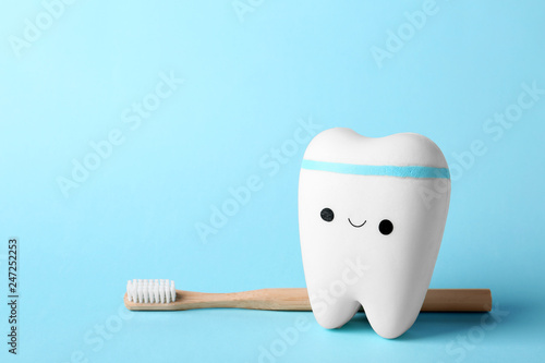Fotografie, Obraz  Model of tooth with happy face, brush and space for text on color background