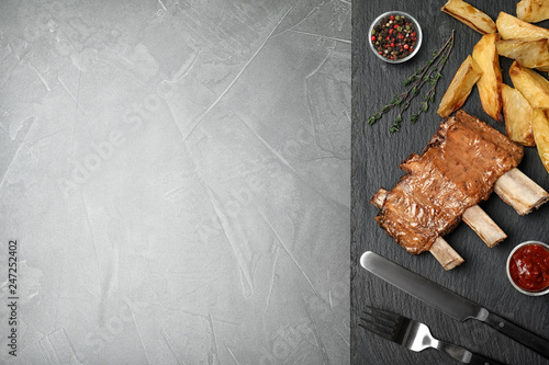 Roasted ribs, sauce and garnish served on table, top view with space for text. Tasty meat