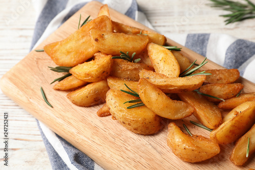 In de dag Aromatische Wooden board with baked potatoes and rosemary on table, closeup