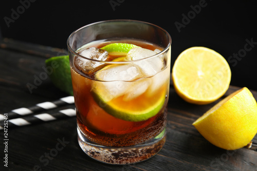 Glass of cocktail with cola, ice and cut lime on table against black background