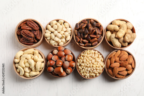 Bowls with different organic nuts on white wooden background, top view. Snack mix