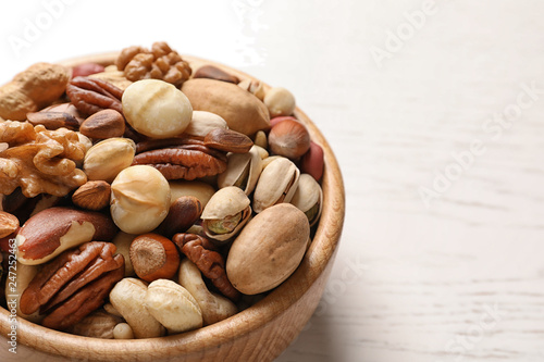 Bowl with organic mixed nuts on table, closeup. Space for text