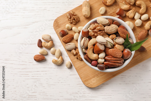 Bowl with organic mixed nuts on table, top view