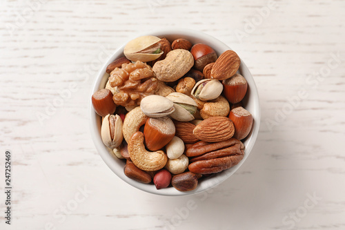 Bowl with organic mixed nuts on white wooden background, top view
