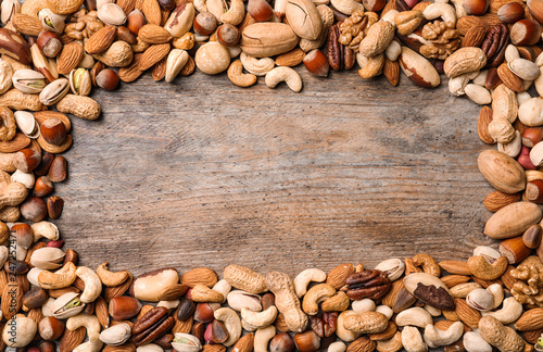 Frame made of organic mixed nuts on wooden background, top view. Space for text
