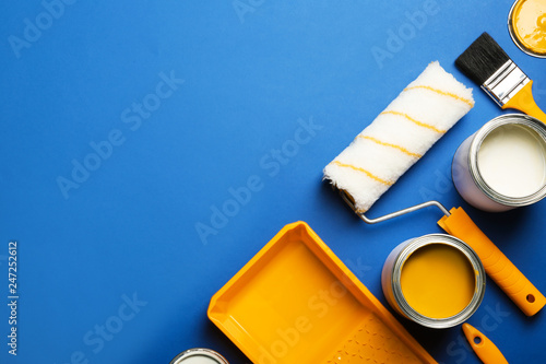 Obraz Flat lay composition with paint cans, decorator tools and space for text on color background - fototapety do salonu