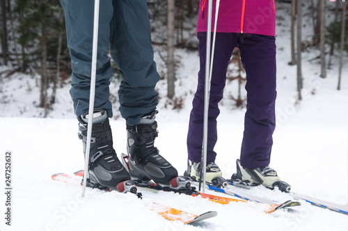 Couple of skiers on slope at resort, closeup. Winter vacation