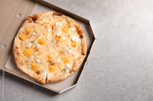 Carton box with hot cheese pizza Margherita on grey table, top view. Space for text