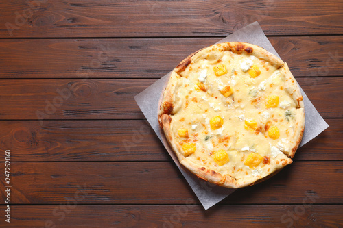 Hot cheese pizza Margherita on wooden table, top view. Space for text