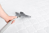 Man disinfecting mattress with vacuum cleaner, closeup. Space for text