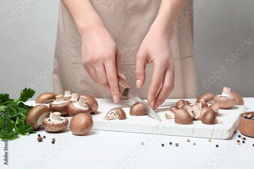 Young woman cutting fresh champignon mushrooms on wooden board, closeup view