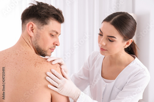 Fényképezés  Doctor examining patient in clinic. Visiting dermatologist