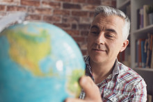 Man Holding A Globe And Findin...