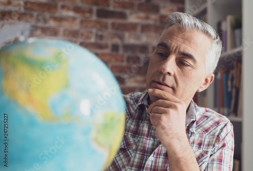 Man holding a globe and finding locations