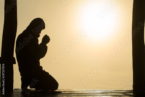 Fotografie, Obraz  Silhouette of young  human hands  praying to god  at sunrise, Christian Religion concept background