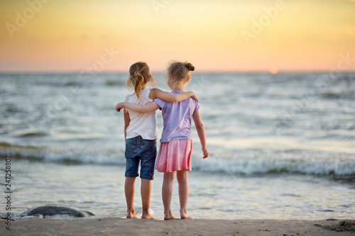 Two cute young sisters having fun on a sandy beach on warm and sunny summer day by the sea. Kids playing by the ocean.
