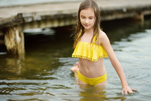 Cute Young Girl Wearing Swimsuit Playing By A River On Hot Summer Day. Adorable Child Having Fun Outdoors During Summer Vacations.