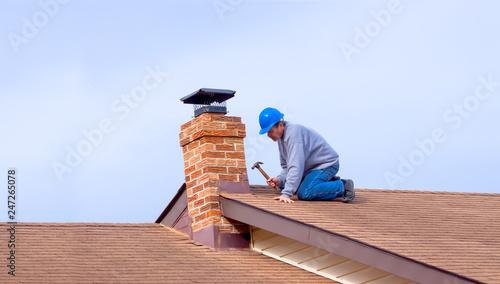 Fotografia, Obraz Contractor Builder with blue hardhat repaoiring roof