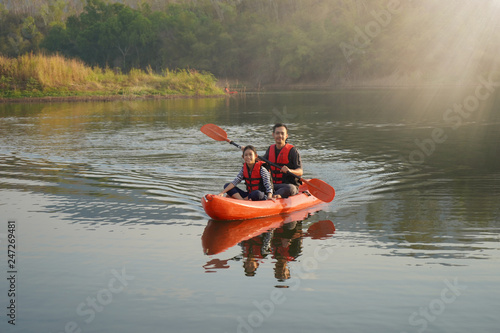 Father and daughter rowing boat on calm waters