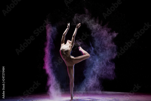 Majestic dancing woman in colorful flying powder