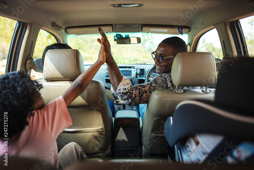 Cheerful family in a car on a road trip