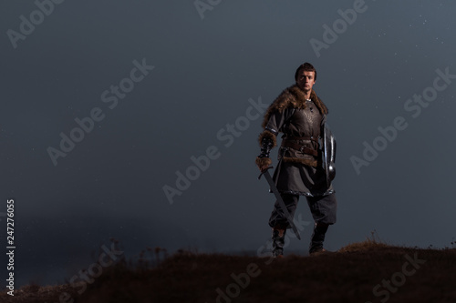 Fotografía Medieval knight with sword and spear in ancient armour over Winter Landscapes