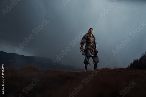 Canvas Medieval knight with sword and spear in ancient armour over Winter Landscapes