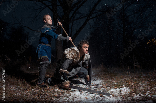 The battle between medieval knights in the style of Game of Thrones in winter forest landscapes Tablou Canvas