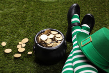 Girl With Leprechaun's Striped Socks Standing On Grass Next To A Black Cauldron Full Of Golden Coins