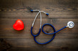 Heart health, health care concept. Stethoscope near rubber heart on dark wooden background top view