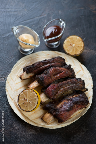 Barbecued beef ribs with dipping sauces on tortilla flatbread, studio shot