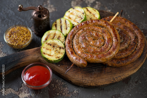 Rustic wooden serving board with grilled coiled sausages, zucchini slices and dipping sauces, studio shot