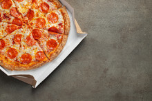 Tasty Pepperoni Pizza In A Box On Brown Concrete Background. Top View Of Hot Pepperoni Pizza. With Copy Space For Text. Flat Lay