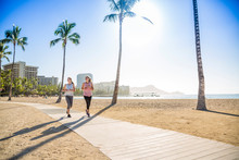 Two Women Jogging On The Beach...