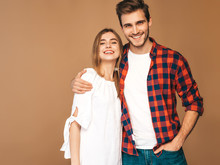 Portrait Of Smiling Beautiful Girl And Her Handsome Boyfriend Laughing.Happy Cheerful Family. Valentine's Day. Posing On Beige Wall. Hugging