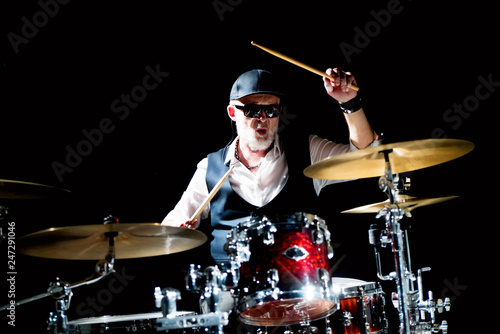Fotografía Professional drummer playing on drum set on stage on the black background