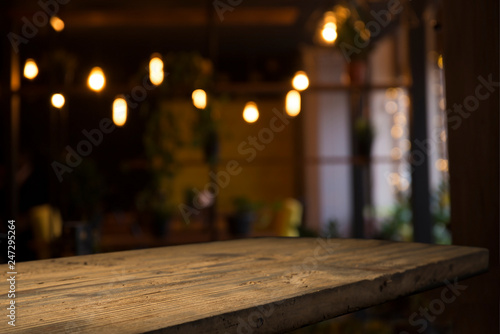 Fototapety, obrazy: image of wooden table in front of abstract blurred background of resturant lights