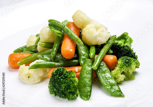 Steamed vegetables on white background. Cauliflower, peas, broccoli, carrots and asparagus beans.