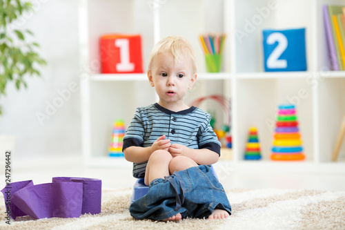 Photo Funny child boy sitting on chamber pot with toilet paper rolls